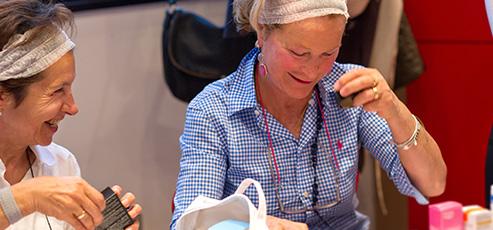 due donne in trattamento oncologico si truccano durante il laboratorio de La forza e il sorriso